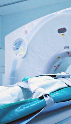 Médico observa paciente entrando em aparelho de tomografia
