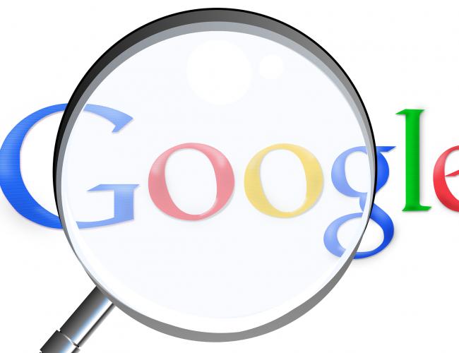 Imagem de uma lupa sobre a palavra Google, na página de busca